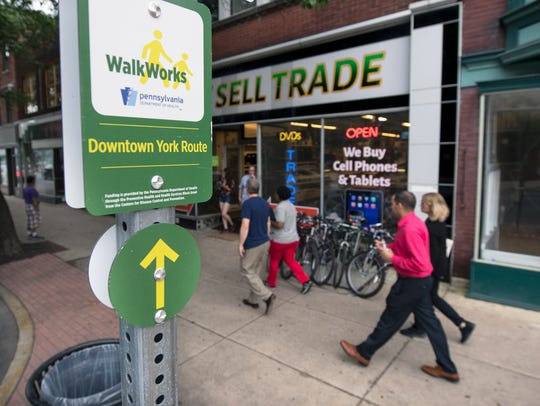 A WalkWorks sign on West Market Street provides arrows