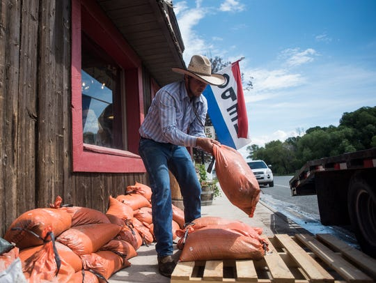 Paul Jones moves sandbags away from Latico and Lace's storefront during flooding in Augusta.