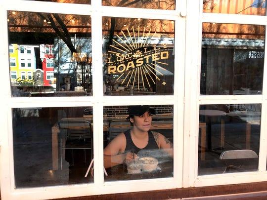 Rebekah Harriot peers out the window of Hillside Coffee