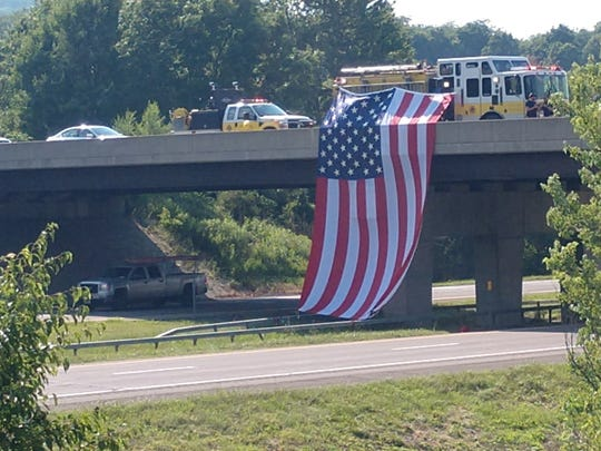 The Apalachin Fire Department unfurled an enormous American flag from the overpass at Exit 66 on Route 17 West in honor of slain Trooper Nicholas Clark.