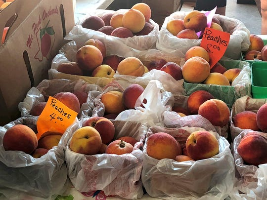 Baskets, bags and boxes of peaches were for sale by