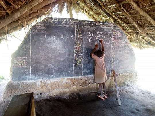 A child works on blackboard that is a large piece of slate at the orphanage school in Togo.