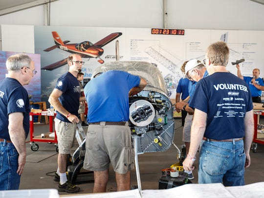 A group of volunteers works on building a plane Saturday,