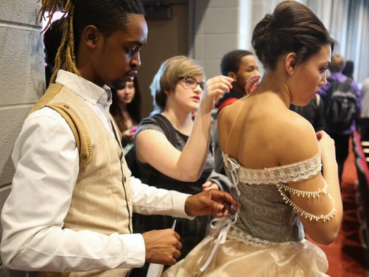 "Pleasure Ridge Park High School student and fashion designer De'Sean ""Ta-Jae"" Isom, from left, and Maggie Colston make final adjustments to a dress designed by Isom and worn by Alexis Vines during the PRP High School's new Fine Arts Building dedication ceremony. ""It's very inspirational that the government is actually trying to influence us and our arts,"" Isom said. ""They want to see us grow and produce wonderful art for the school and the community."" March 7, 2014"