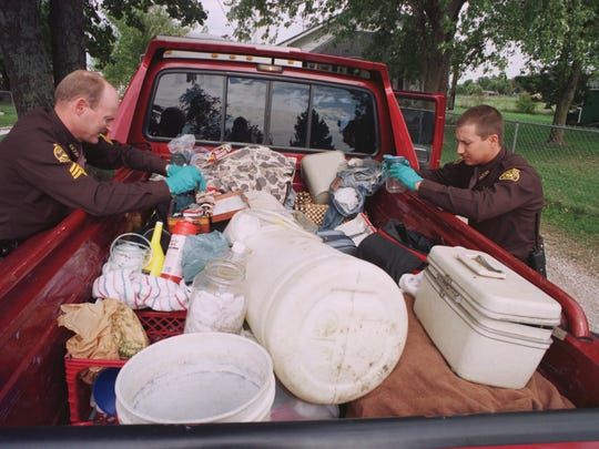 In this 1998 photo, deputies with the Greene County Sheriff's Office sort through meth-making equipment in the back of a pickup for which they had been searching.
