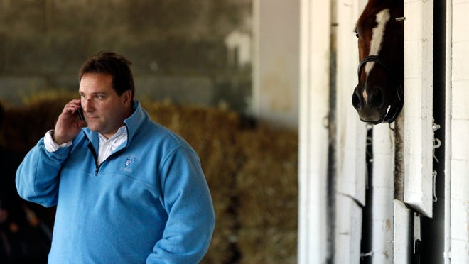 Local trainer Mike Maker speaks on his cell phone at Churchill Downs in 2010.
