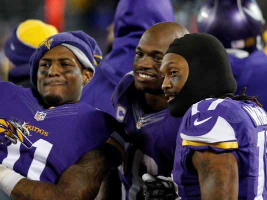 FILE - In this Dec. 27, 2015, file photo, Minnesota Vikings wide receiver Mike Wallace (11), running back Adrian Peterson (28) and wide receiver Jarius Wright (17) react on the sideline during the second half of an NFL football game against the New York Giants in Minneapolis. The Vikings hosted the Giants at the ninth-coldest game in their history. (AP Photo/Ann Heisenfelt, File)