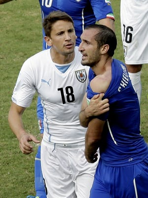 Italy's Giorgio Chiellini, right, shows his shoulder after being bitten by Uruguay's Luis Suarez's mouth as Uruguay's Gaston Ramirez (18) watches during the group D World Cup soccer match between Italy and Uruguay at the Arena das Dunas in Natal, Brazil, Tuesday, June 24, 2014.