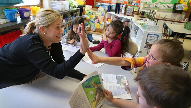 First-grade teacher Nicole Williams gives a high-five to student Eden Falco after she finished her reading exercise in their classroom at Lima Primary School in the village of Lima Tuesday, April 19, 2016.