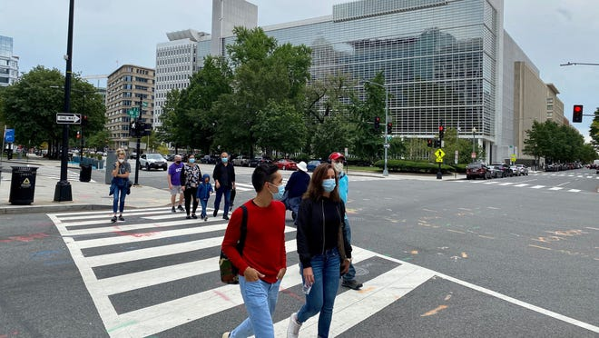 People wearing masks cross the road front of the World Bank Group building in Washington, D.C., in September amid the COVID-19 crisis.