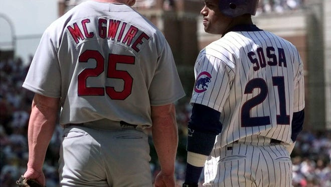 In this May 28, 1999, file photo, Chicago Cubs' Sammy Sosa, right,  and St. Louis Cardinals' Mark McGwire (25) chat at first base after Sosa singled in the second inning of a baseball game at Wrigley Field in Chicago.