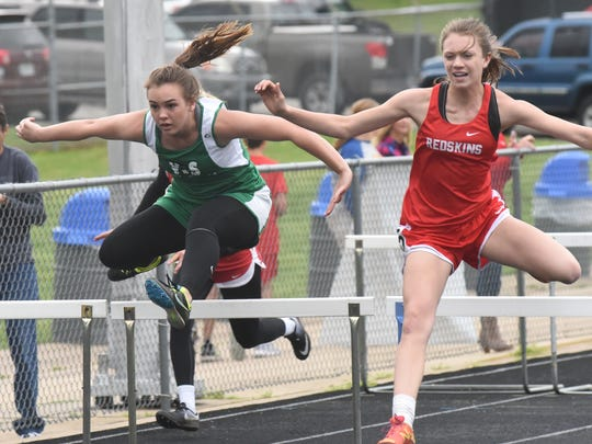 Yellville-Summit's Justina Jenkins (left) competes in the 100-meter hurdles.