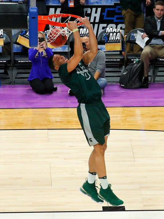 Michigan State guard Miles Bridges dunks during practice at the NCAA college basketball in Detroit, Thursday, March 15, 2018. Michigan State plays Bucknell in the first round on Friday.  (AP Photo/Paul Sancya)