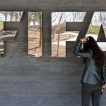 A journalist waits in front of the FIFA logo at the FIFA Headquarters in Zurich, Switzerland.