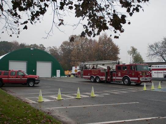 Emergency vehicles are shown at a temporary storage