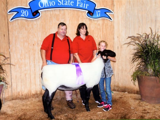 Kelcie Hopper and her Suffolk ewe, Breezie are pictured with her aunt and grandfather at the Ohio State Fair in a family photo.