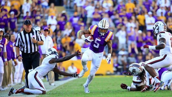 LSU Tigers running back Derrius Guice (5) breaks a tackle against the South Carolina Gamecocks during the fourth quarter of a game at Tiger Stadium. LSU defeated South Carolina 45-24.