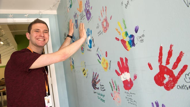 Bryan Epstein is pictured at his job as a community outreach educator at Project R.E.A.L. in Asbury Park. Here, he mimics making hand prints on the wall. These prints were made by Project members as a way of leaving their mark, Epstein said.