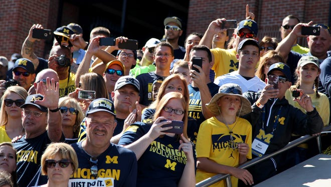 Michigan fans photograph coach Jim Harbaugh and the team before a game against Penn State at Michigan Stadium in Ann Arbor on Saturday, Sept. 24, 2016.