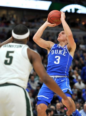 Duke guard Grayson Allen shoots as Michigan State guard Cassius Winston (5) watches during the first half of an NCAA college basketball game Tuesday, Nov. 14, 2017, in Chicago.