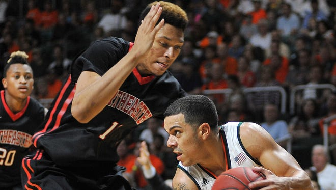 Miami guard Angel Rodriguez, right, attempts to get by Northeastern's Jeremy Miller on Nov. 27, 2015.
