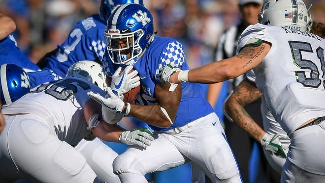 Kentucky Wildcats running back Benny Snell Jr. (26) avoids several Eastern Michigan Eagles defenders for positive yards during the game at Kroger Field on the campus of the University of Kentucky in Lexington, Ky, Saturday, September 30, 2017.