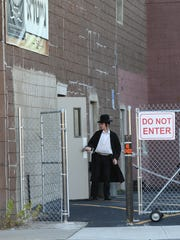 A man walks into the yeshiva at 50 Commerce St. in