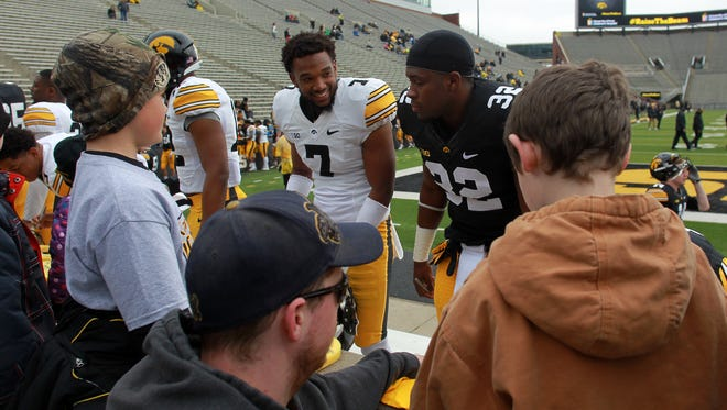Iowa's Sean Draper (7) and Derrick Mitchell Jr. (32) sign autographs prior to the Hawkeyes' spring game at Kinnick Stadium on Saturday. Mitchell rushed for 53 yards on seven carries.