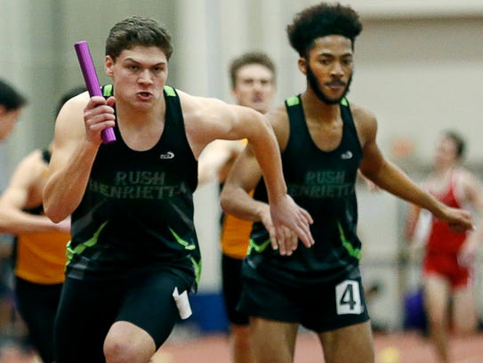 Rush-Henrietta's Ben Hulbert taking the baton from Stephan Beckham during the Section V Class A and D Indoor Track Championships.