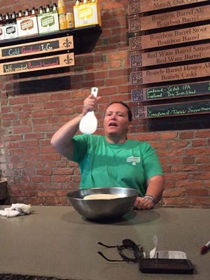 Sushi instructor Kelly Viall demonstrates how to mix vinegar into rice for sushi.