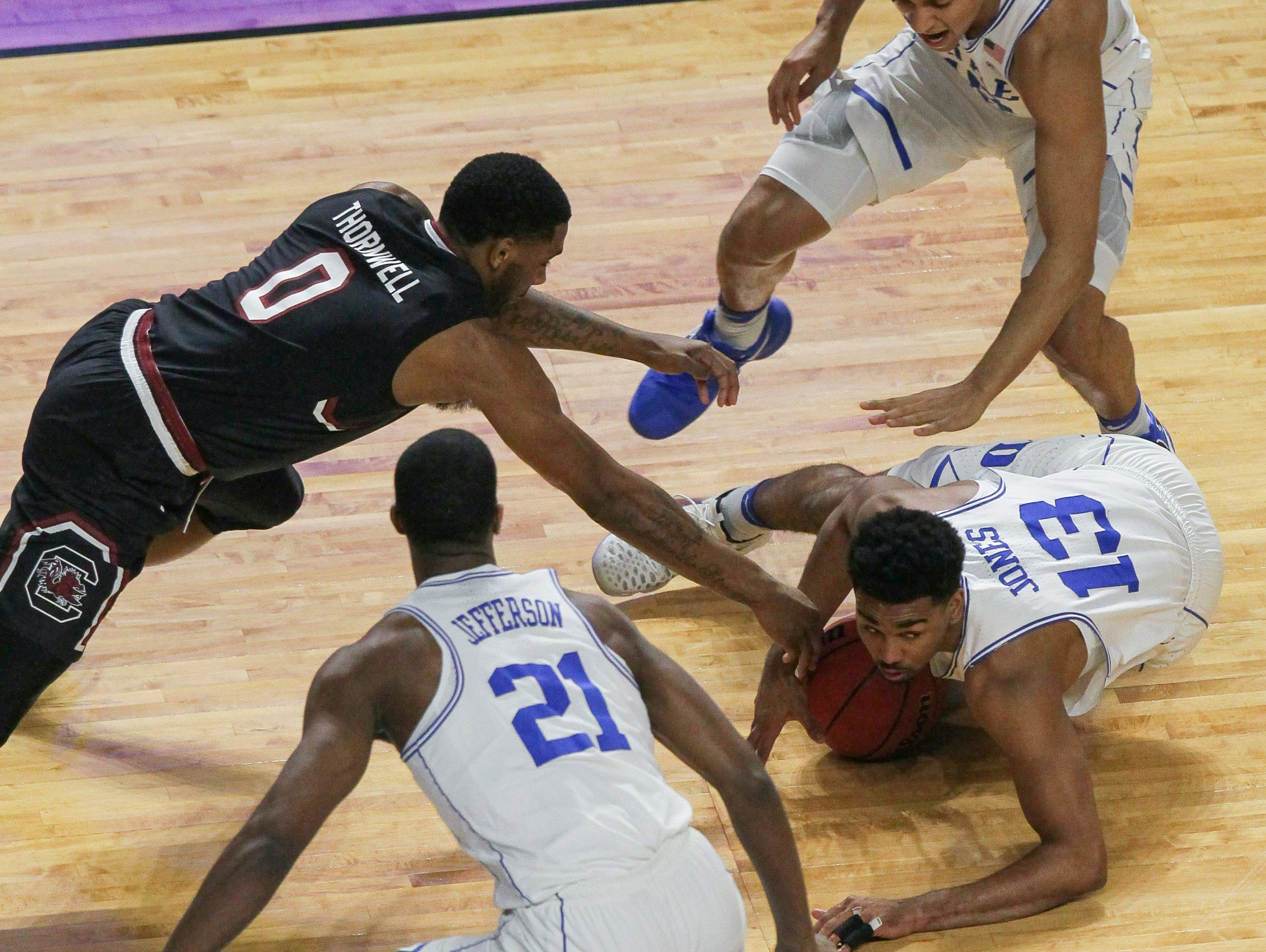 South Carolina guard Sindarius Thornwell (0) reaches in for a loose ball with Duke guard Matt Jones (13) in the first half during the 2nd round of the NCAA Tournament at Bon Secours Wellness Arena in downtown Greenville on Sunday, March 19, 2017.