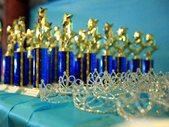 Crowns and trophies, along with sashes lined a table