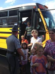 Students leave a school bus at Oakdale Baptist Church after a shooting at Townville Elementary School.