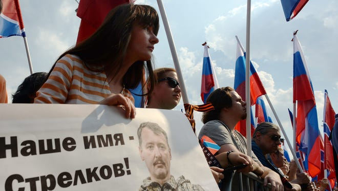 """A woman holds a poster with the portrait of Igor Strelkov, the top military commander of the self-proclaimed Donetsk People's Republic and with the slogan """"Our name is Strelkov"""" during a rally of support in Moscow on Aug. 2, 2014."""