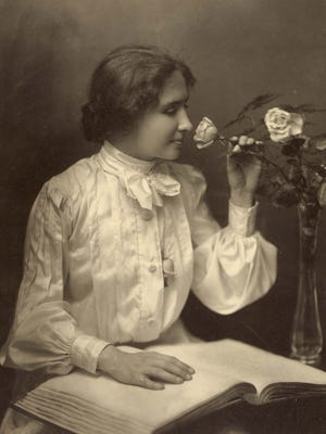 Circa 1904 photograph showing Helen Keller seated with one hand on a braille book as she smells a rose in a vase. At the request of her niece, who was a Mary Baldwin College student, Keller spoke to a large crowd at the First Presbyterian Church in 1942.
