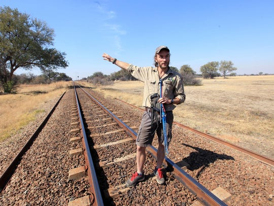 Lion researcher Brent Staplekamp holds an antenna while