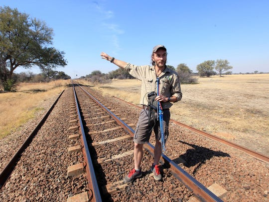 Lion researcher Brent Staplekamp holds an antenna while standing on the tracks that Cecil the lion crossed when he was lured onto a farm in an alleged illegal hunt in Zimbabwe.