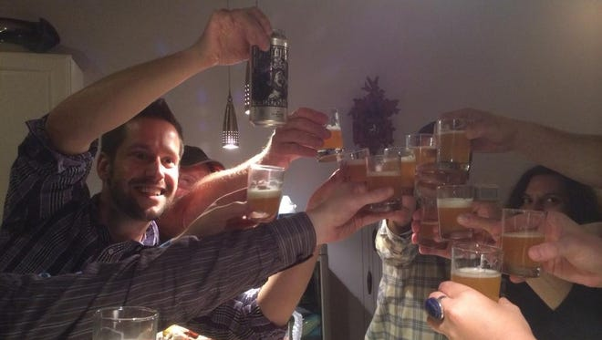 The Beer Guy and friends make a toast during a recent craft beer tasting party.