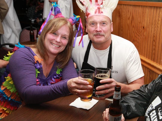 Tina and Murray  Cummins sit with their friend, Amy Dugan and enjoy a drink during the BCMAMS Crawl-o-Ween Saturday night.