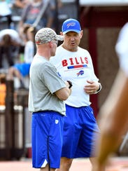 Rick Dennison and Sean McDermott plotting during training