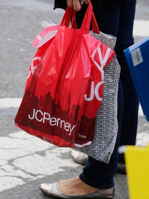 A shopper carries a J.C. Penney bag, Tuesday, April 9, 2013 in New York.