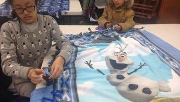 Youden and Jigme Shawa, ages 12 and 6, work on an Olaf character blanket.