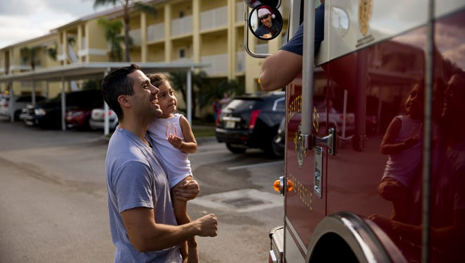Will Zanetti and his daughter Valentina Zanetti Cruz, 2, are all smiles after receiving candy canes from driver engineer John Richard, a firefighter with Greater Naples Fire Rescue Station 73, as they drive around Laurel Lakes and Key Royal Villas on Sunday, Dec. 24, 2017, in North Naples.