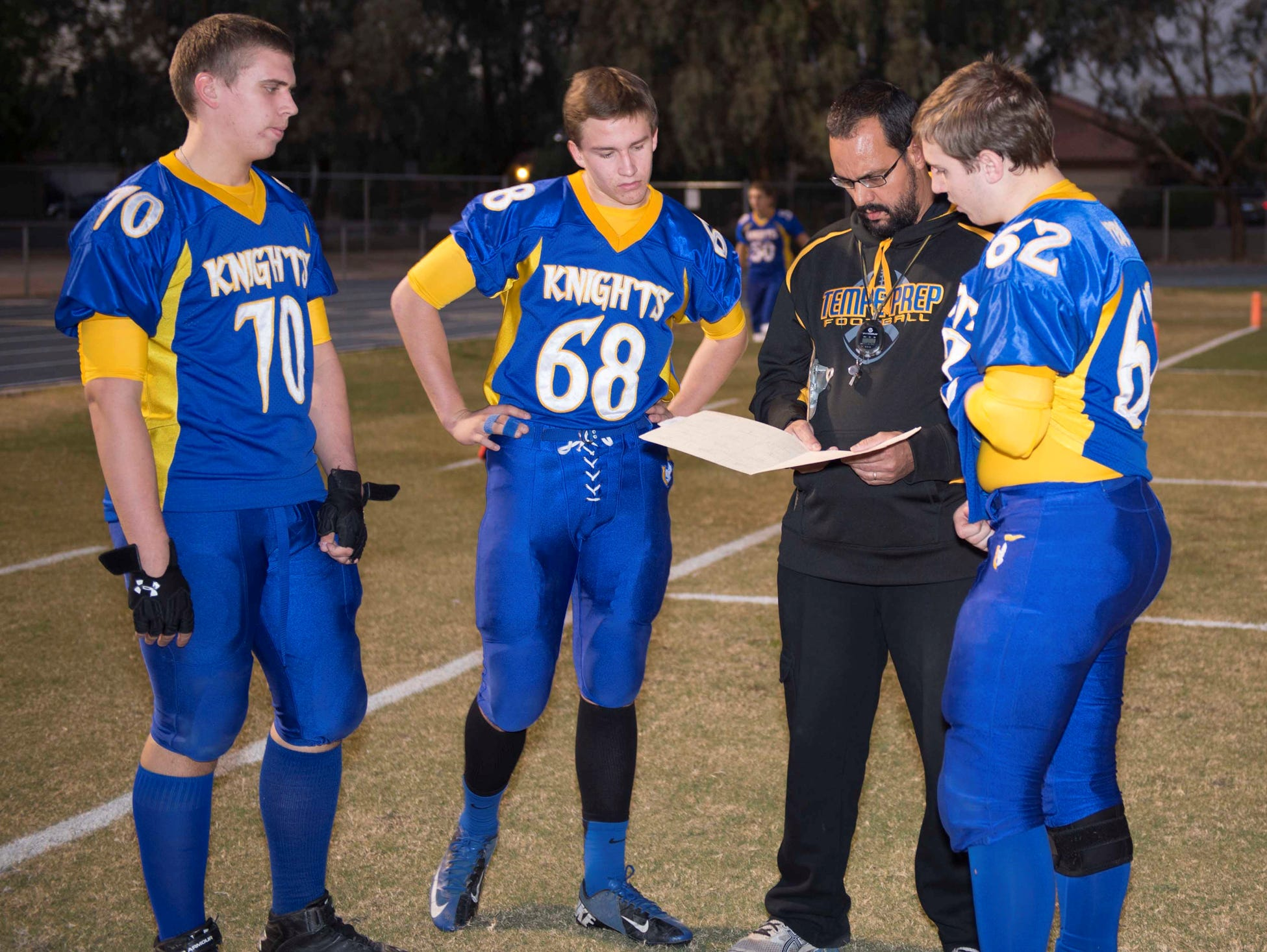 Tempe Prep football players (from left) Andrew Stough, Connor Woltz and Christian Gaylor huddle around coach Tommy Brittain.