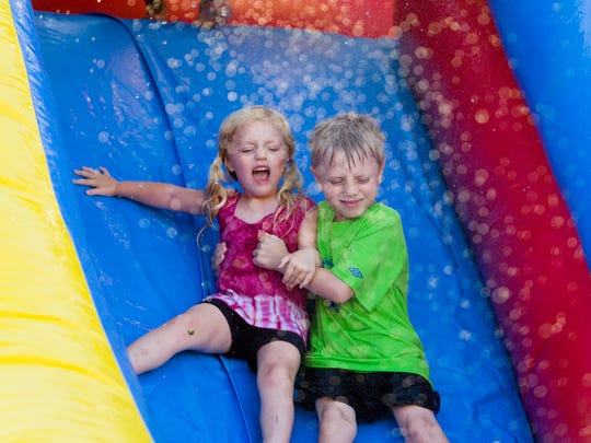Hailey (age 3) and Ben (age5) of Mannington, NJ enjoy a water slide at Family Fun Day at Carousel Park in Pike Creek on Saturday.