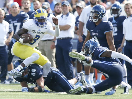 Delaware quarterback Joe Walker (left) bowls past Villanova's Don Cherry (44) and Rob Rolle before being tackled on a 16-yard run in the quarter of the Blue Hens' 28-21 loss at Villanova last Saturday.