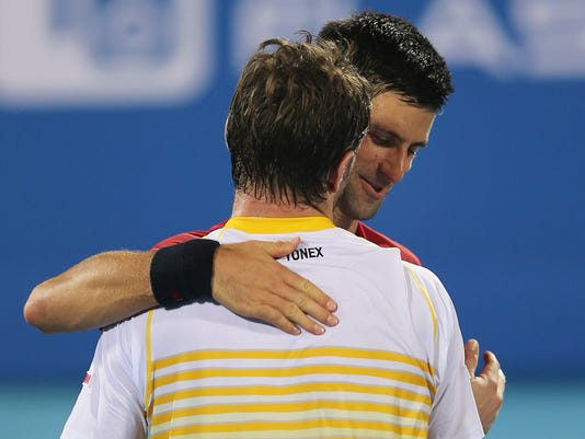 Serbia's Novak Djokovic comforts Stanislas Wawrinka of Switzerland after he beats him on the second day of the Mubadala World Tennis Championship in Abu Dhabi, United Arab Emirates, Friday, Jan. 2, 2015. (AP Photo/Kamran Jebreili)