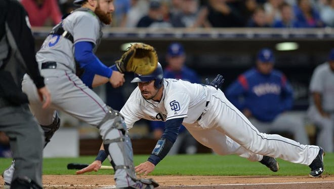 Padres catcher Austin Hedges (right) slides ahead of the throw to Rangers catcher Jonathan Lucroy (left) during Monday's second inning.
