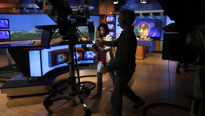 """WHAM-TV will move its morning and 10 p.m. news shows from the local CW affiliate to WUHF, Fox Rochester, beginning Jan. 1. Both stations are now owned by Sinclair Broadcast Group. Above, Claire Tseng, left, and Jeff Sprague wheel cameras in the WHAM news studio after a segment last month. The morning show will be rechristened """"Good Day Rochester."""""""