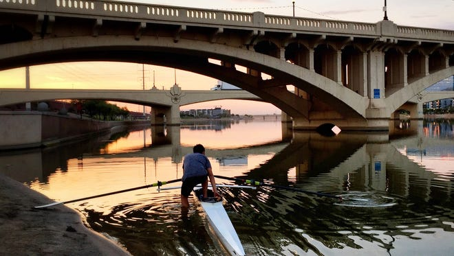 A member of the Tempe Junior Crew puts his scull in the water at sunrise on June 20, 2017, at Tempe Town Lake. The temperature was already 86 degrees.